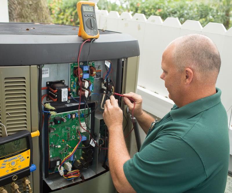 Technician repairing an outside A/C unit