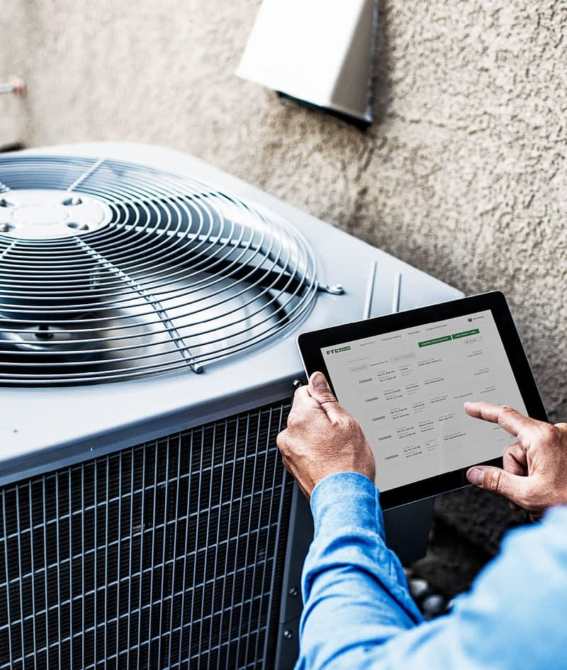 Man standing infront of an A/C unit holding a tablet